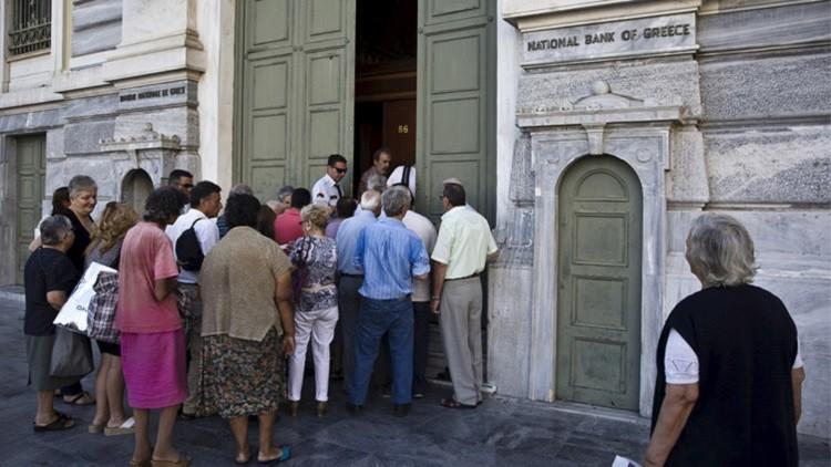 يونانيون ينتظرون الدخول إلى أحد فروع البنك الوطني في أثينا بتاريخ 20 يوليو/تموز