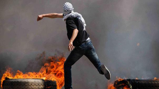 فلسطيني يرشق حجرا على جنود الاحتلال