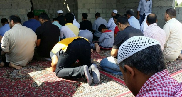 مواطنون يقيمون صلاة الظهرين في موقع مسجد عين رستان المهدم إبان فترة الطوارئ
