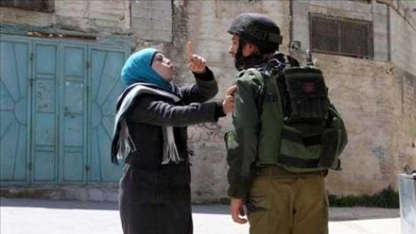 صورة ارشيفية لجندي صهيوني يعتدي على فلسطينية