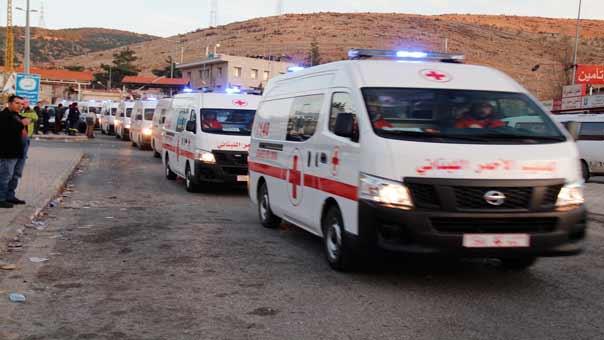 سيارات الصليب الاحمر اللبناني التي تقل جرحى مسلحي الزبداني عند نقطة المصنع اللبناني